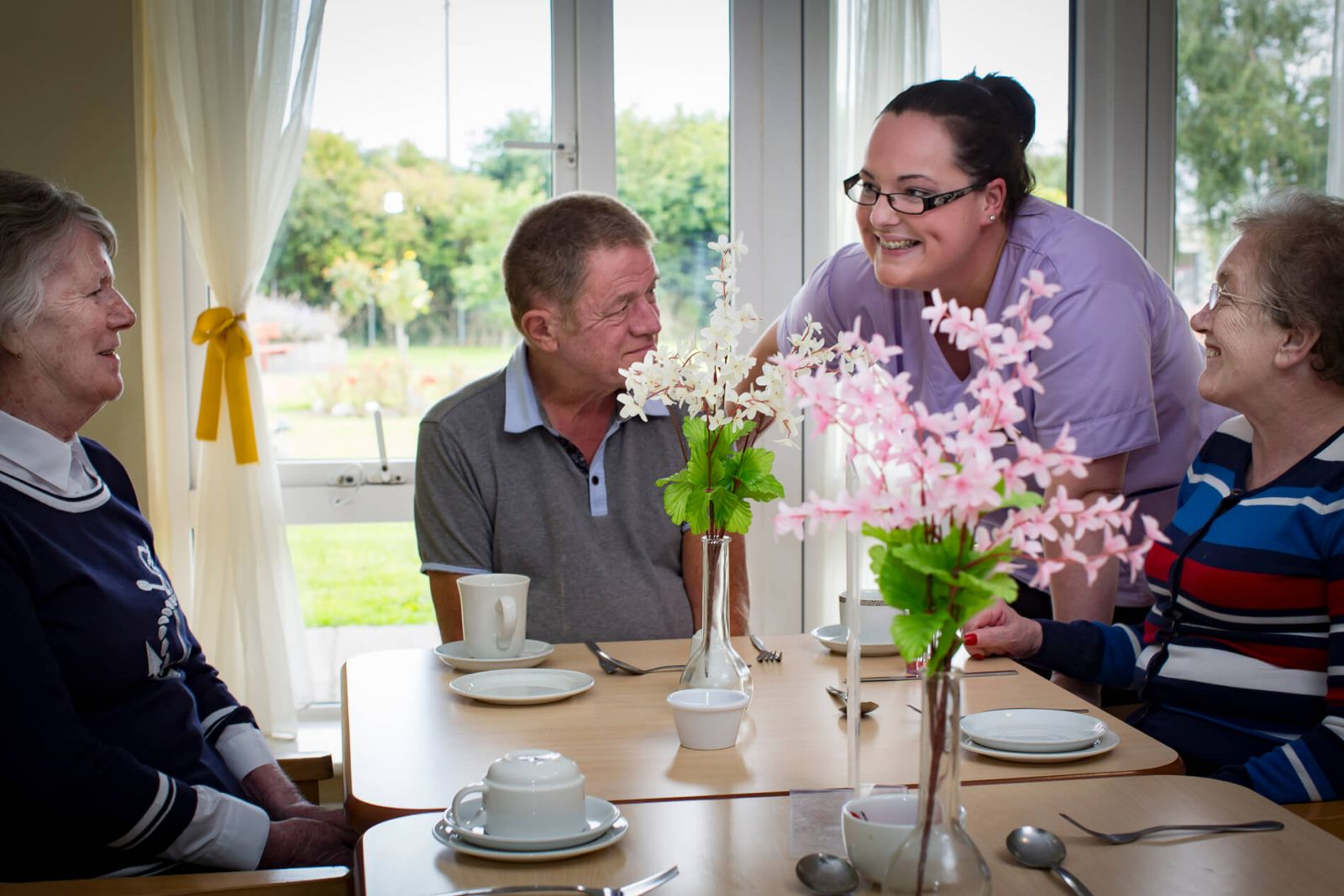 care work smiling with three residents sitting at a table with beautiful pink flowers
