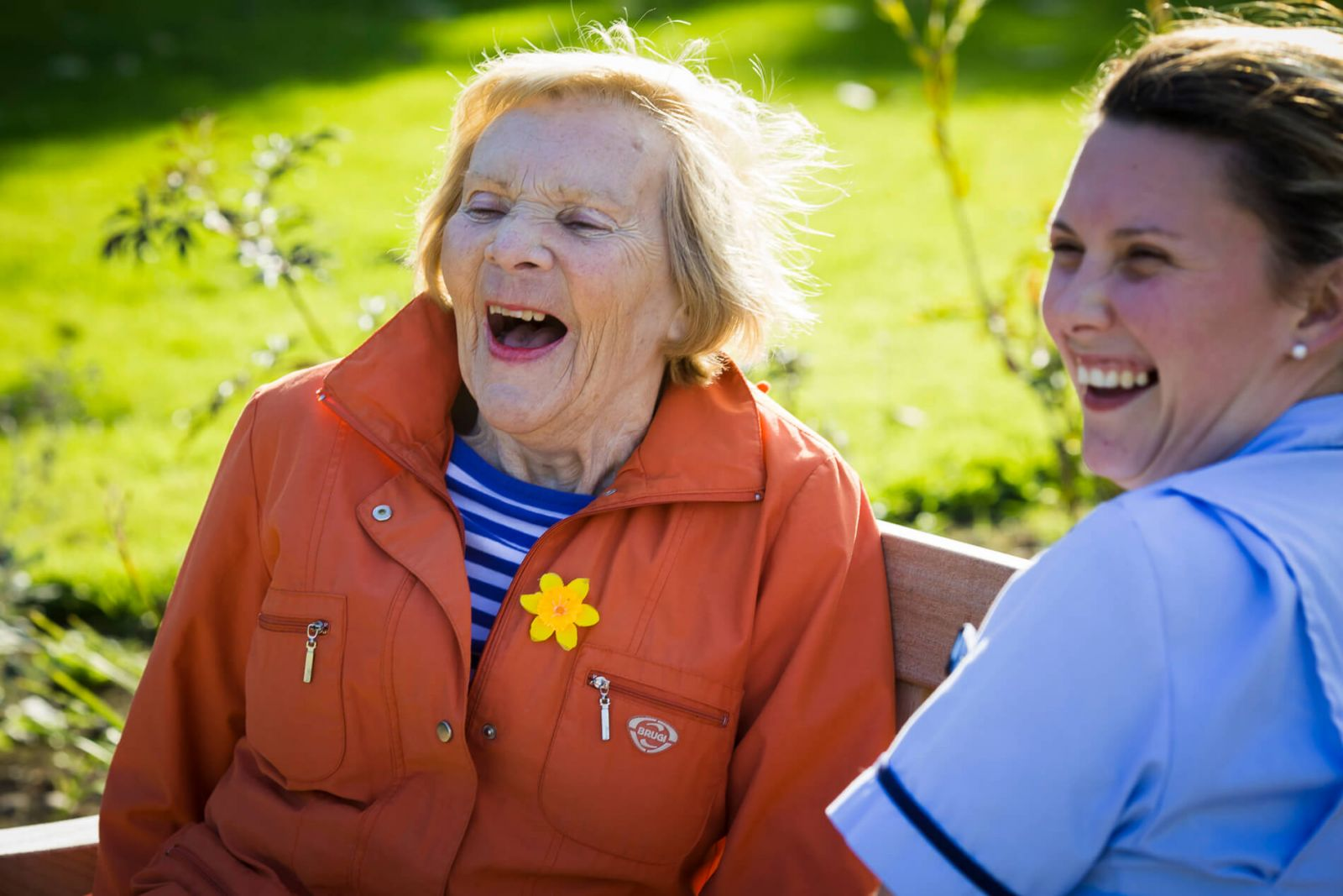 nurse and resident having a laugh in the garden
