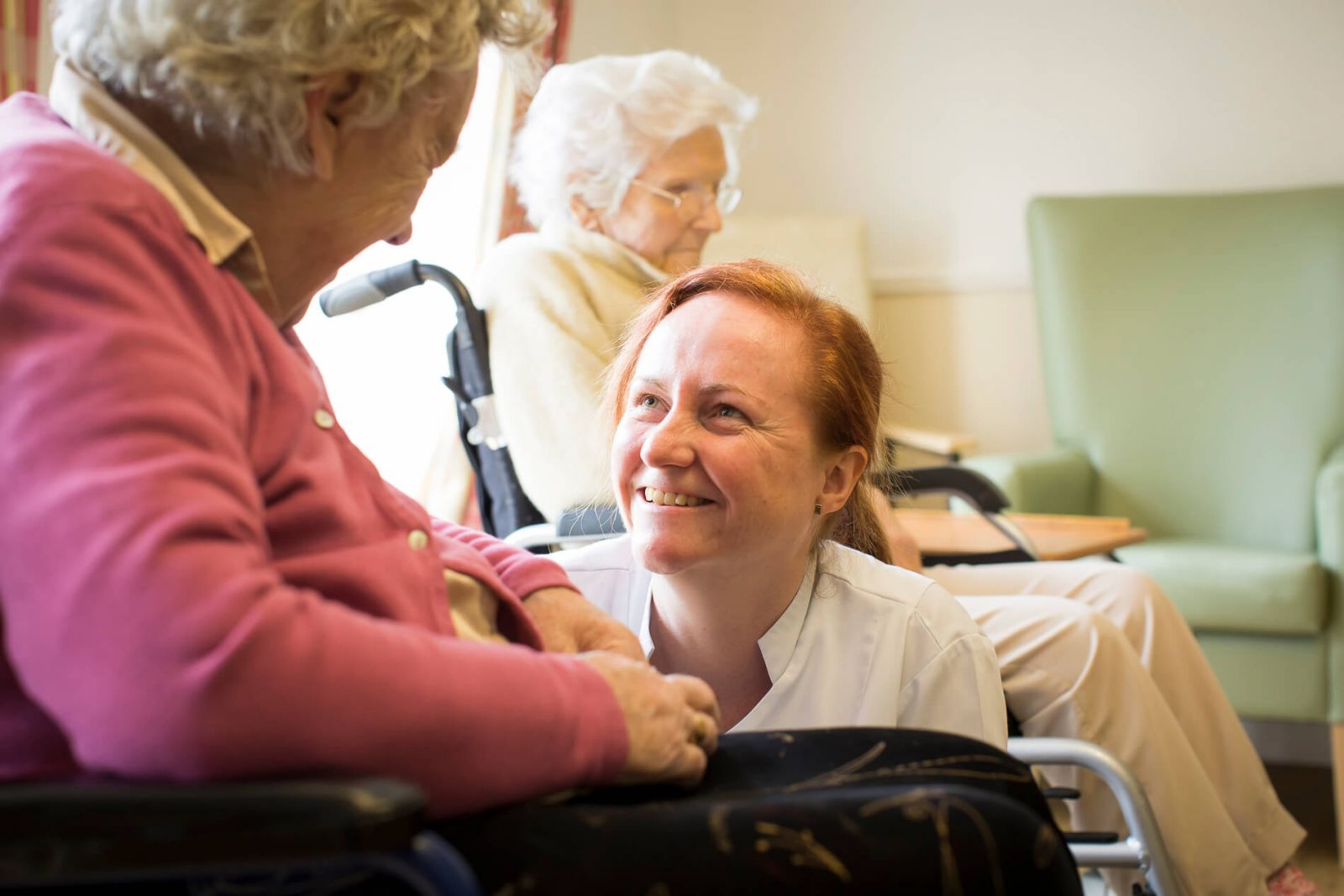nursing smiling and talking with resident in wheelchair