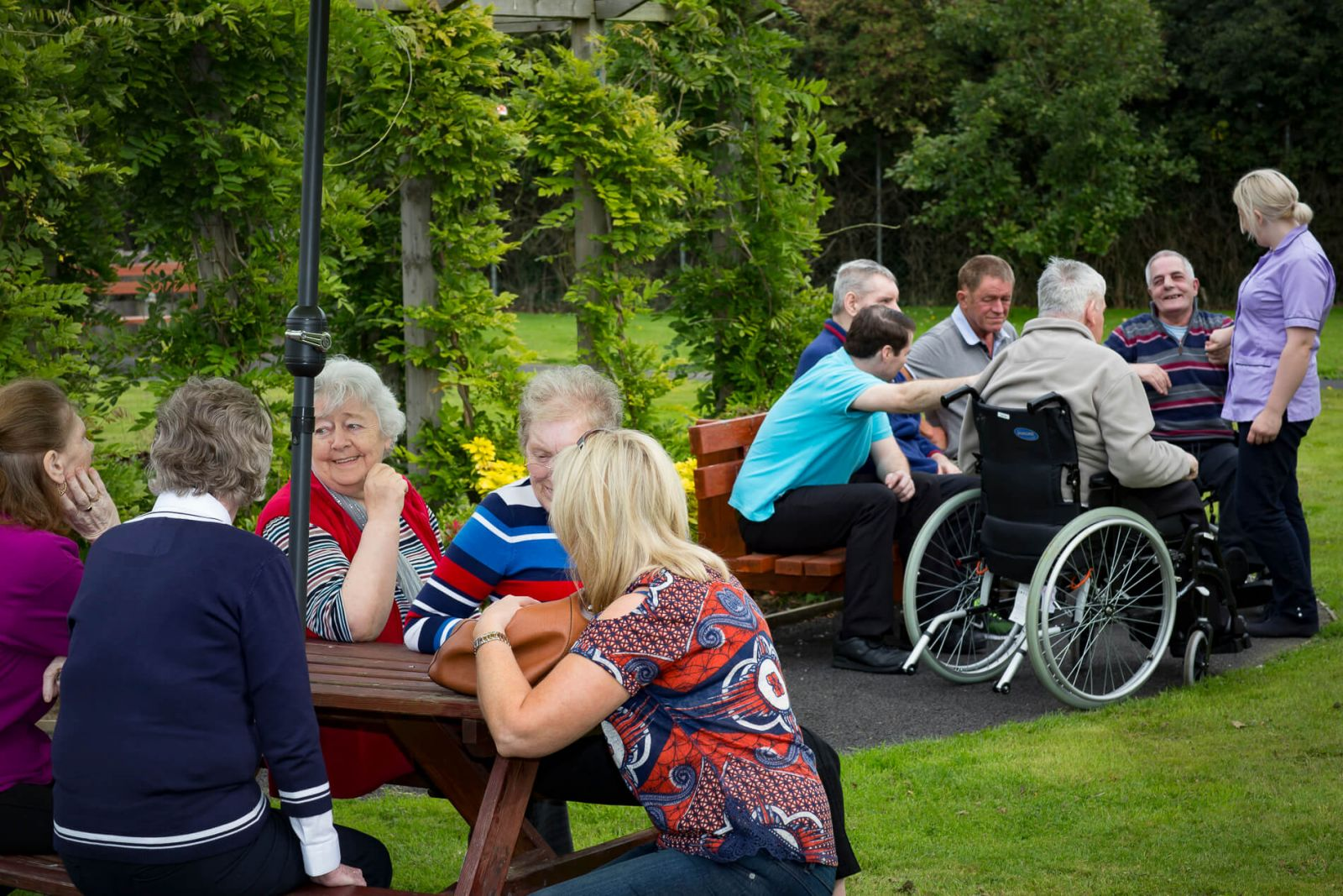 residents and their friends and families in the garden interacting