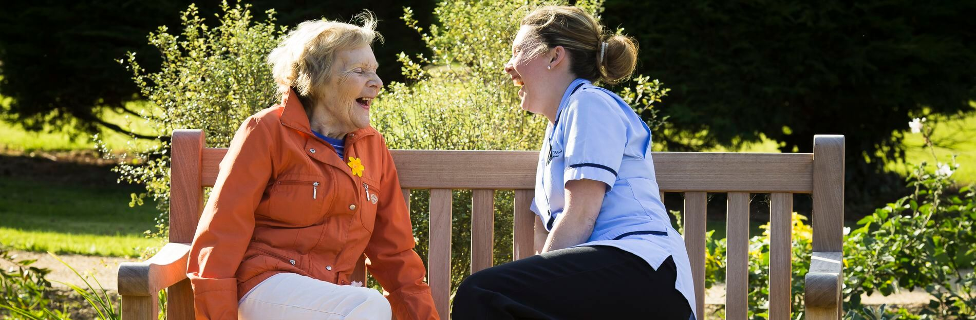 Care Worker laughing with resident in garden