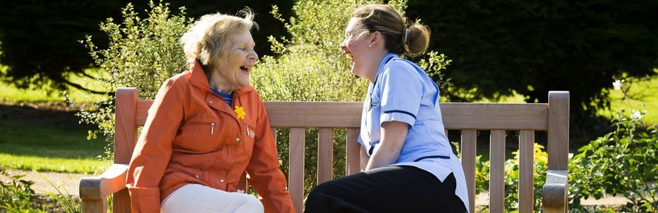 Nurse and female resident laughing in garden sitting on bench